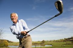 senior adult man holding golf club - stock photo