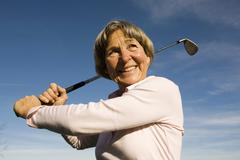 Senior adult nainen, jolla golf club Kuvituskuvat
