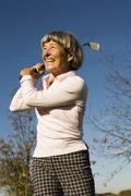 Senior adult woman holding golf club Stock Photos