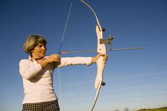 senior adult woman using bow and arrow, side view - stock photo