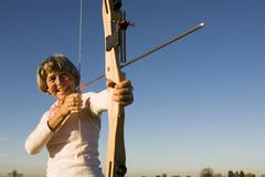 senior adult woman using bow and arrow - stock photo