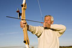 senior adult man using bow and arrow - stock photo