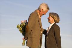 Senior couple, man hiding bouquet, smiling, side view Stock Photos