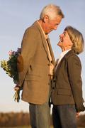 Stock Photo of senior couple, man hiding bouquet, side view