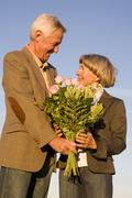 Senior couple, man giving woman bouquet Stock Photos