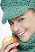 Young woman wearing cap and scarf, holding apple, portrait Stock Photos