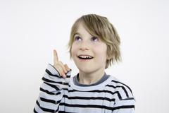 Boy (10-11) pointing and looking upwards, portrait Stock Photos