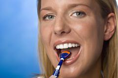 Young woman using tongue cleaner, portrait - stock photo