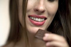 Stock Photo of Young woman holding chocolate candy, portrait