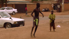 An African man does a bizarre stunt by running up to a wall and doing a flip. Stock Footage