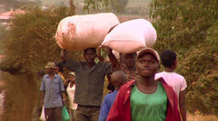 People carry goods on their heads in an African village. Stock Footage