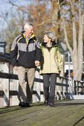 senior couple walking hand in hand on jetty - stock photo