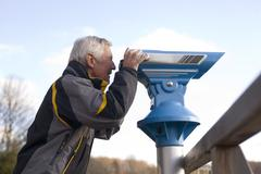 Stock Photo of senior adult man looking through telescope, side view