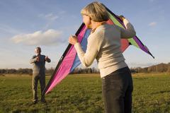 Germany bavaria, ammersee, senior couple flying kite Stock Photos