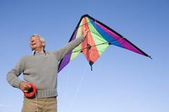 senior man flying kite, smiling, low angle view - stock photo
