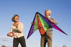 Senior couple, man holding kite Stock Photos