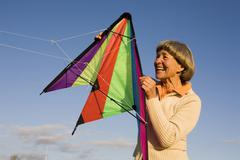 Senior adult woman holding kite, smiling Stock Photos