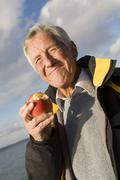 Stock Photo of senior adult man eating apple