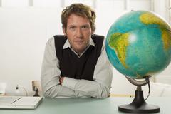 young man sitting on desk, globe in foreground - stock photo