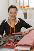 Stock Photo of young woman measuring cloth, smiling, portrait