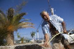 Greece, Crete, Paleochora, Senior man washing car Stock Photos