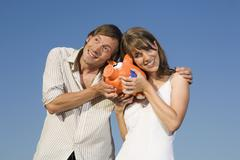 Germany, Bavaria, Young couple holding piggy bank, smiling, portrait Stock Photos