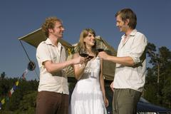 Germany, Bavaria, Friends drinking red wine, smiling, portrait - stock photo