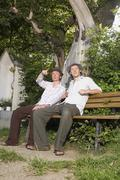 Germany, Bavaria, Young men sitting on bench Stock Photos