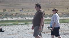 Fat people walking in desert - stock footage