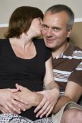 Germany, Hesse, Frankfurt, Pregnant woman kissing man - stock photo