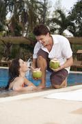 Asia, Thailand, Man handing cocktail to woman in pool - stock photo