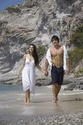 Stock Photo of Asia, Thailand, Young couple walking hand in hand along beach