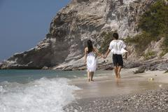 Asia, Thailand, Young couple walking hand in hand along beach, rear view - stock photo