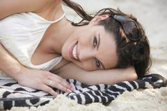 Asia, Thailand, Young woman lying on beach, smiling, portrait - stock photo