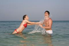 Stock Photo of Asia, Thailand, Young Couple in ocean, splashing water