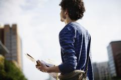 Germany, Berlin, Young man holding city map - stock photo