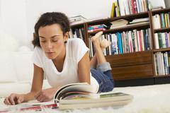 Young woman lying on floor, reading Stock Photos