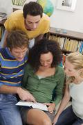 group of young people reading book - stock photo