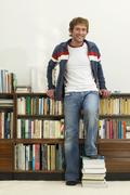 Young man standing in front of bookshelf, feet on books, portrait Stock Photos