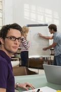 Young man explaining woman chart in background, focus on man smiling Stock Photos