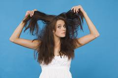 Stock Photo of Young woman tearing her hair, portrait