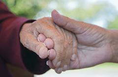 Senior women holding hands, close-up - stock photo