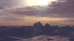 Stock Video Footage of Sunset behind a frozen tundra scene in the Arctic.