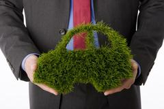Person holding Car symbol made from grass, close-up - stock photo