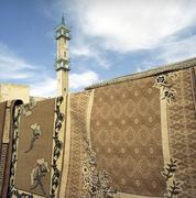 Stock Photo of Jordan, Amman, Traditional carpets with minaret in background