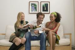 three young people sitting on sofa - stock photo