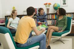 Four young people sitting in circle Stock Photos
