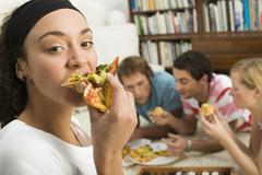 Four young people lying on floor, eating pizza Stock Photos