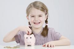 Stock Photo of Girl (4-5) putting coin into piggy bank, smiling, portrait