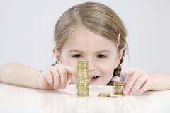 Girl (4-5) counting stack of coins Stock Photos